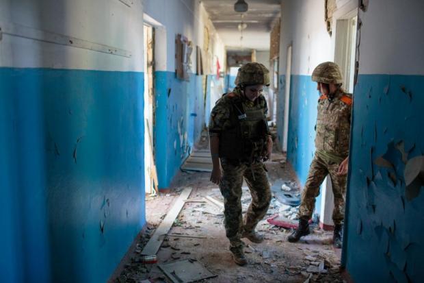 Два офіцера ЗСУ йдуть через коридор в школі у Широкиному
