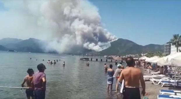 Люди з пляжу спостерігають за пожежею